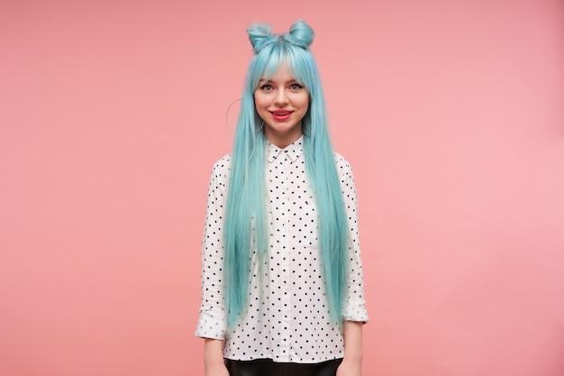 Bella giovane donna dai capelli lunghi in camicia bianca con punti neri che guarda allegramente e sorride sinceramente, indossando i suoi capelli blu in nodi mentre posa