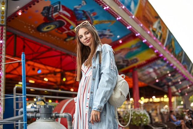 Beautiful young long haired female with sunglasses on her head posing over attractions in amusement park, wearing romantic summer dress and trendy jeans coat