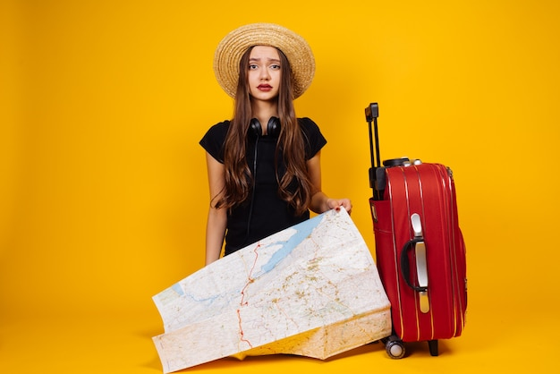 帽子をかぶった美しい若い長い髪の少女は、スーツケースとカードを持って旅行に行きました