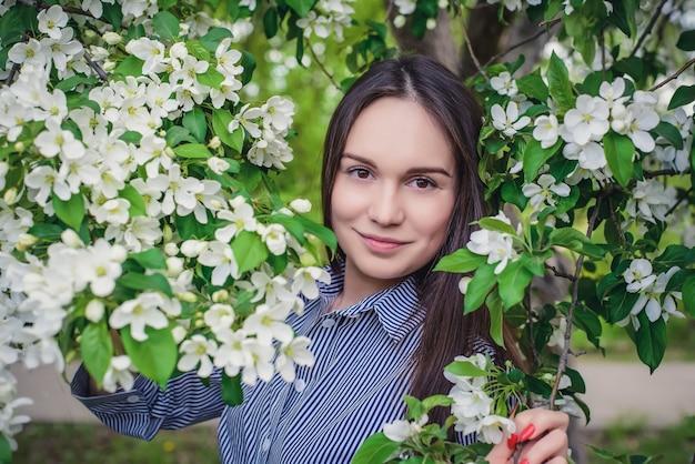 Красивая молодая длинноволосая девушка в синем полосатом платье возле цветущих яблонь весной