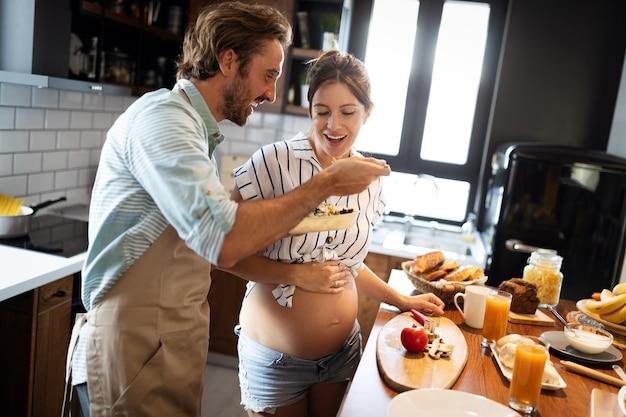 아름다운 젊은 사랑스러운 커플이 집에서 부엌에서 건강한 음식을 요리하는 동안 이야기하고 웃고 있습니다