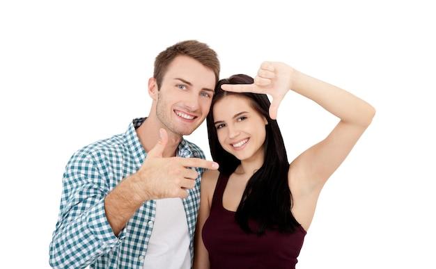 아름다운 젊은 연인들이 합류하고 웃고 있으며, 그들의 손에서 프레임을 만들고 있습니다.
