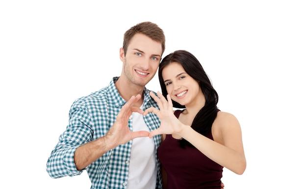 아름다운 젊은 연인들이 합류하고 웃고 있으며, 그들의 손에서 하트 프레임을 만들고 있습니다.