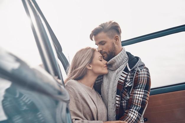 Красивая молодая влюбленная пара обнимается, стоя возле микроавтобуса на открытом воздухе