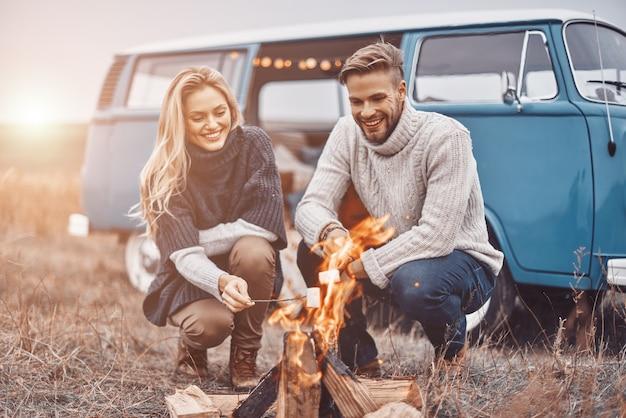 Красивая молодая влюбленная пара на пикнике у костра, сидя возле своего ретро-минивэна