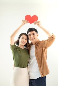 美しい若い愛情のあるカップルは、白い壁にハートの形をしたカードを持っています。