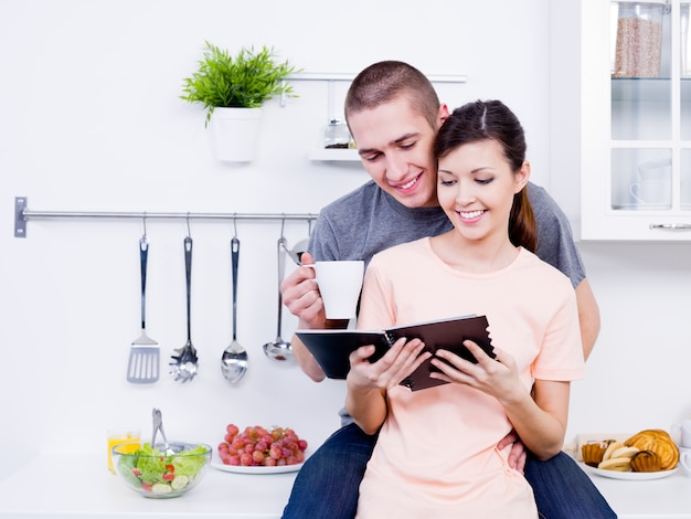 Belle giovani coppie amorose che leggono insieme il libro di cucina in cucina