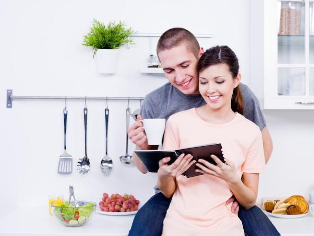 キッチンで一緒に料理本を読んで美しい若い愛情のあるカップル