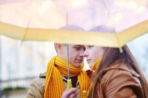 Beautiful young loving couple under an umbrella in the rain