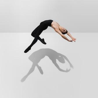 ジャンプ、空中飛行の影と白いスタジオの背景で練習している美しい若い男性アスリート