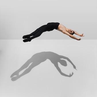 점프 그림자, 공기 비행 흰색 스튜디오에서 연습하는 아름 다운 젊은 남자 선수