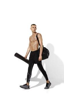 影と白で練習する美しい若い男性アスリート Premium写真