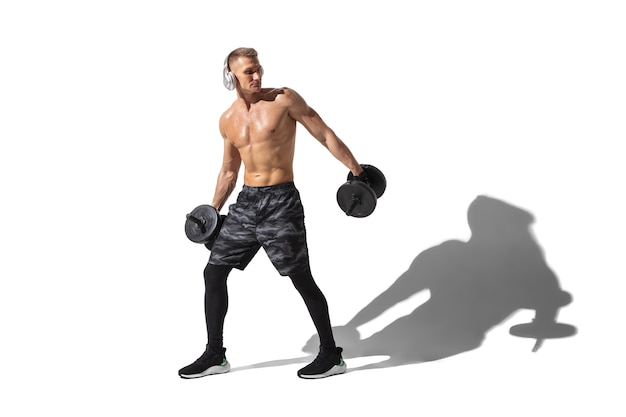 Beautiful young male athlete practicing on white studio background with shadows