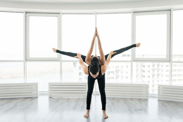 美しい若い男性と女性の練習ペア大きな窓と一緒に白いフィットネススタジオでペアアクロヨガの練習