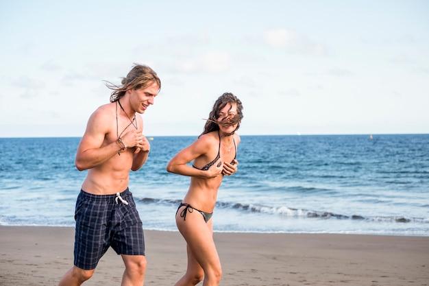 夏休みを一緒に楽しんでいるビーチで遊びに走る美しい若い男女