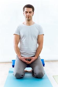 Beautiful young man practicing yoga at home. vajrasana pose.