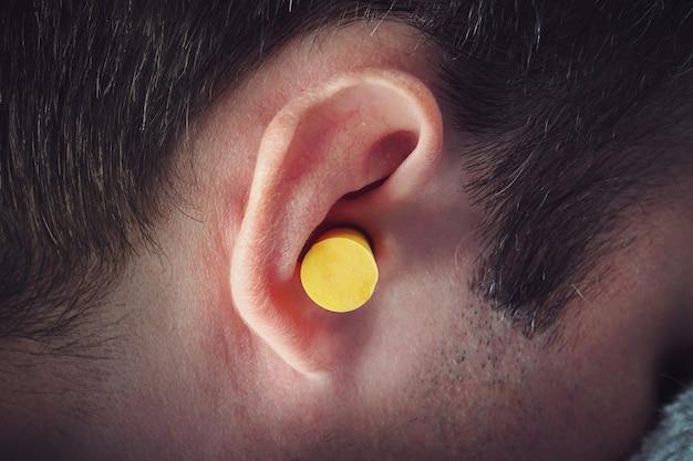 잠을 방해할 때 거리 소음에 대한 노란색 귀마개에서 자고 있는 아름다운 청년.