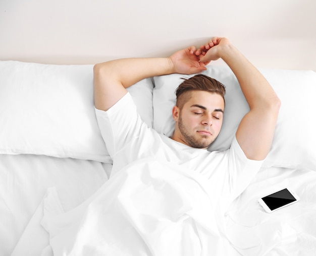 아름 다운 젊은 남자가 침대에서 졸고 프리미엄 사진