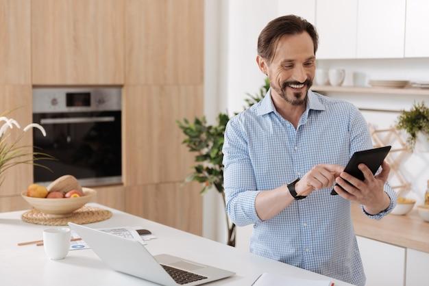 Красивый молодой человек, стоящий на кухне и листающий веб-страницы на своем планшете, удивленный содержанием