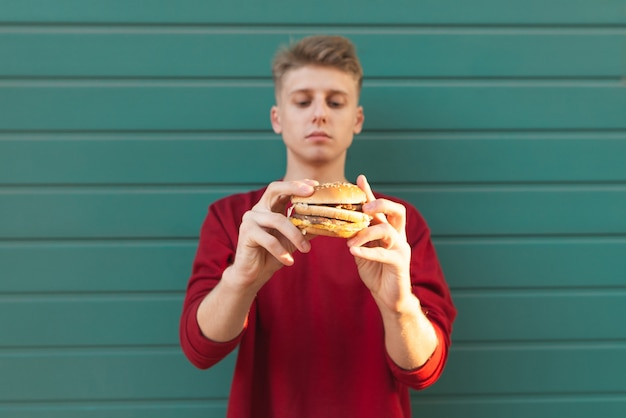 美しい若い男が立って、食欲をそそるハンバーガーを保持します