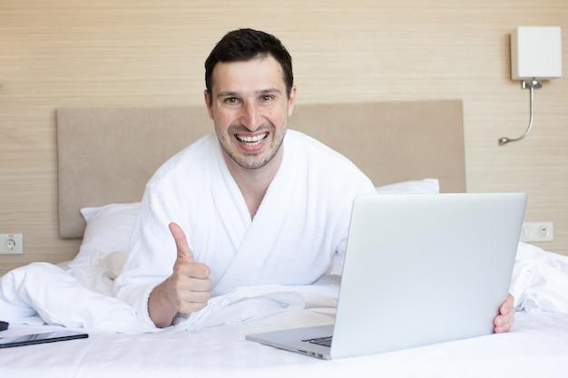 침대에 누워있는 동안 노트북을 사용하는 아름 다운 젊은 남자.
