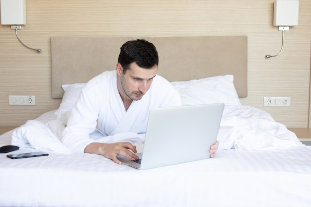 ベッドに横たわっている間ラップトップを使用して美しい若い男。