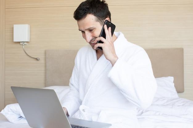 침대에 앉아있는 동안 노트북을 사용하는 아름 다운 젊은 남자.