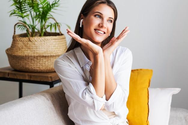 美しいミレニアル世代の少女は、ソファの上でリラックスした位置に座っています。大変な一日を過ごした後、女性は休んでいます。白いシャツを着た女の子は家にいてとても幸せです。