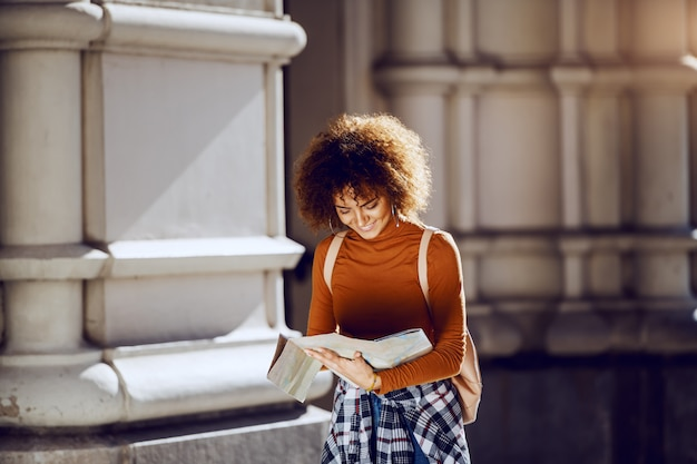 Beautiful young mixed race female tourist with curly hair and bag on back standing in front of old building and looking at map.