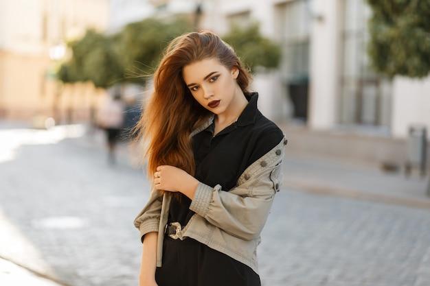 유행 재킷과 도시에서 포즈 검은 폴로 셔츠에 아름 다운 젊은 모델 소녀