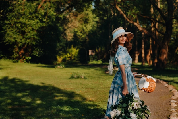 A beautiful young model girl in a straw hat poses in a park with a bouquet of white blooming lilacs on a sunny spring day.