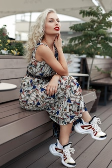 Beautiful young model girl in a stylish dress with fashionable sneakers sits on a wooden bench in the street