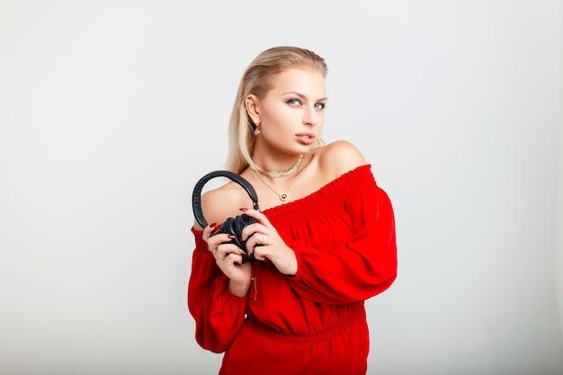 Красивая молодая модель девушка с наушниками в стильном красном платье на сером