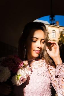 花の花束を保持している美しい若いモデル。彼女の顔に影を付けて通りでポーズをとる女性