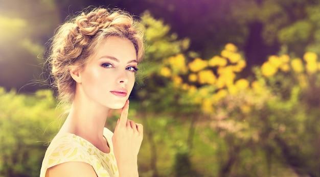 Красивая молодая модель в цветущем весеннем саду.