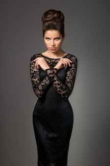 夜のメイクや髪型が灰色の背景にポーズと黒のドレスで美しい若いモデル