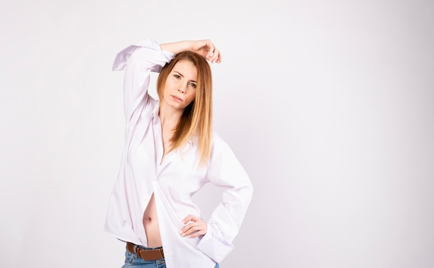 白い背景の上の白いtシャツとジーンズの美しい若いモデル