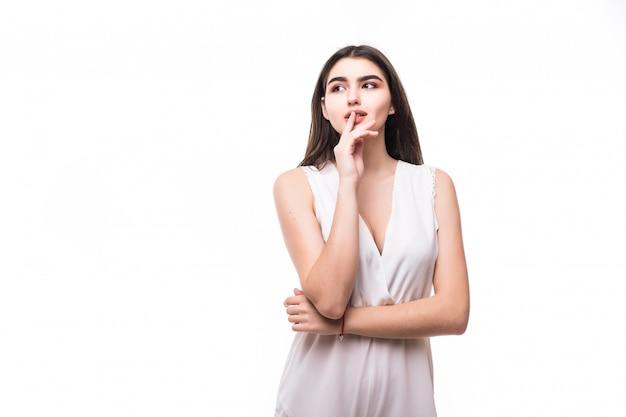 Bello giovane modello in vestito bianco moderno sul pensiero bianco