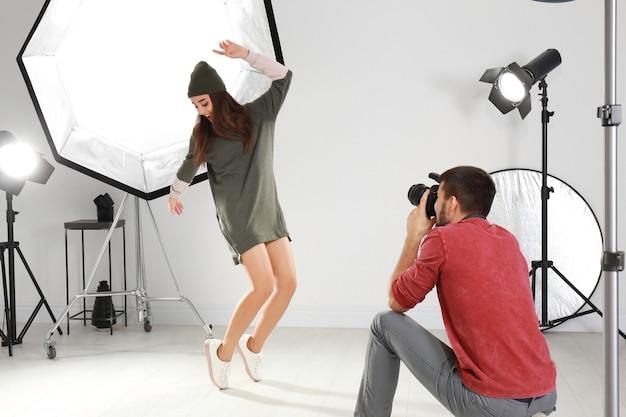 Красивая молодая модель позирует для профессионального фотографа в студии