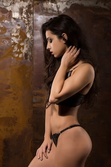 Beautiful young model with fitness body in seductive lingerie posing at studio