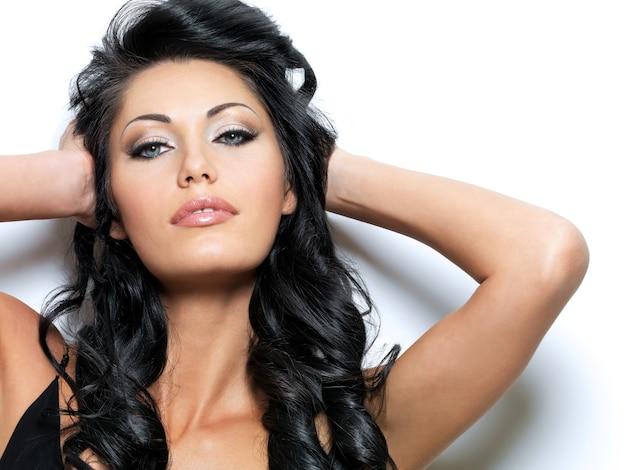 Красивая молодая модель с длинными каштановыми волосами и довольно голубыми глазами.