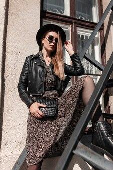 Красивая молодая модель женщина в модной одежде с шляпой и солнцезащитными очками с модной сумочкой позирует на металлической лестнице в солнечный день
