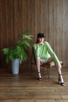 스튜디오에 앉아 포즈를 취하는 아름 다운 젊은 모델 여자