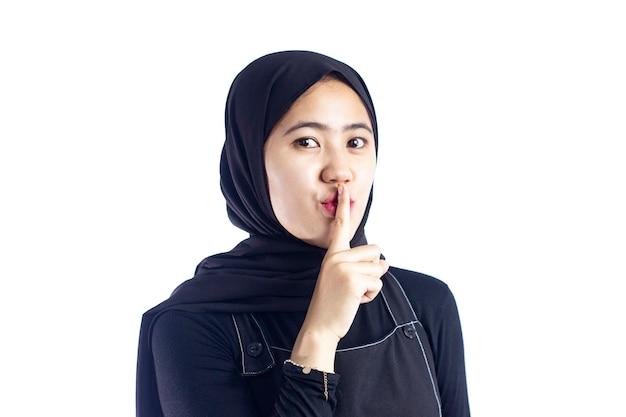 唇に指で静かにすることを求める美しい若い現代のイスラム教徒沈黙と秘密の概念
