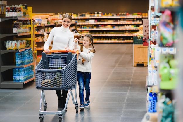 아름 다운 젊은 엄마와 그녀의 작은 딸 웃 고 음식을 구입