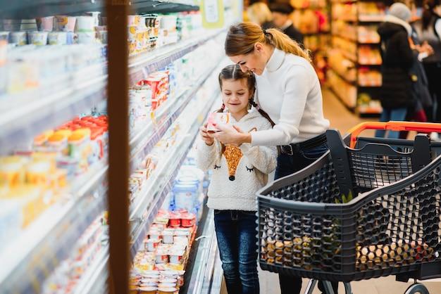 美しい若いお母さんと彼女の小さな娘笑顔と食べ物を買う