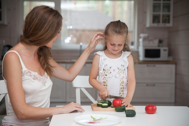 スカンジナビアスタイルのインテリアの白いキッチンで楽しんでサラダ用野菜を準備している美しい若いお母さんと小さな娘。健康食品。