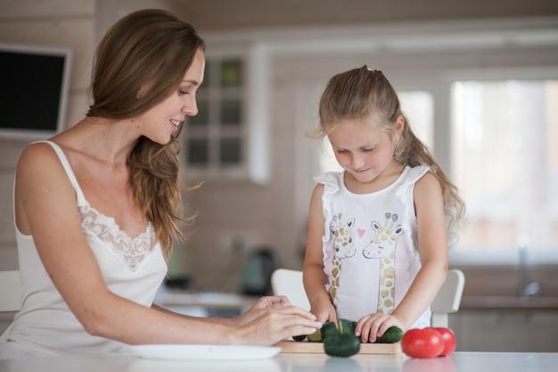スカンジナビアスタイルのインテリアの白いキッチンで楽しんでサラダ用野菜を準備している美しい若いお母さんと小さな娘。