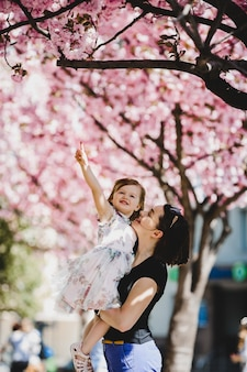Beautiful young mom holds lovely little daughter standing under blooming pink tree