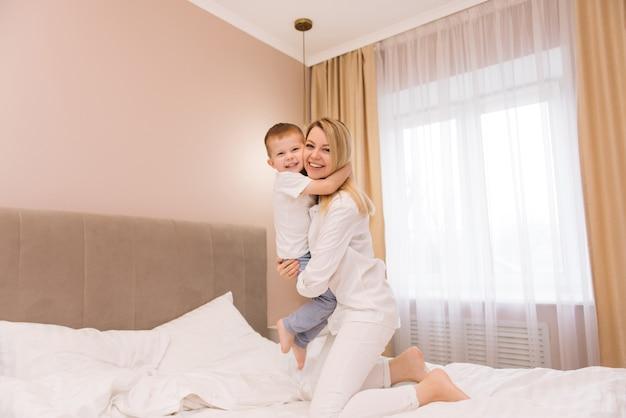 寝室のベッドで赤ちゃんの笑顔の息子と一緒に遊んで笑う美しい若いお母さん、幸せな家族